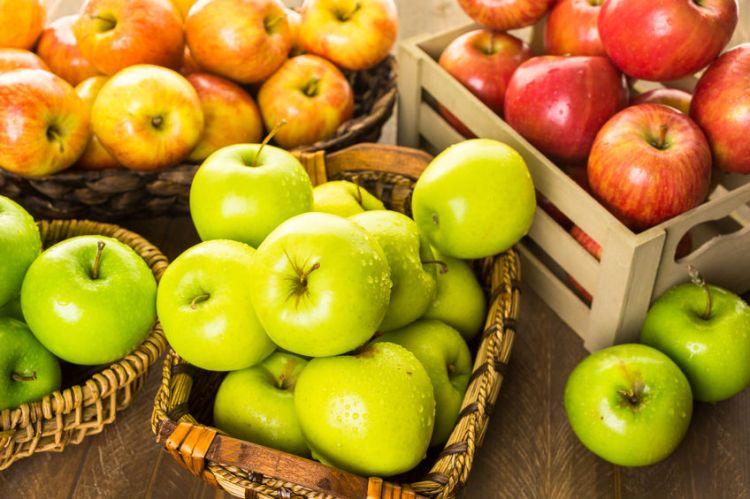 45124268 - variety of organic apples in baskets on wood table.