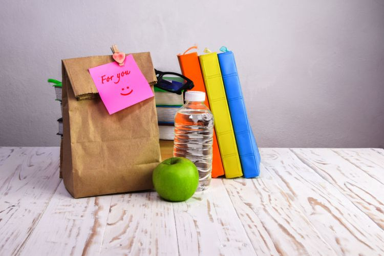 39145209 - paper  lunch bag  with apple,water and books  on desk with  note,