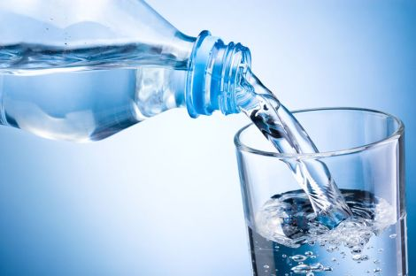 39260451 - close-up pouring water from bottle into glass on blue background